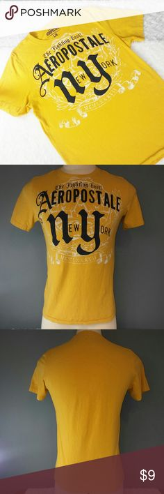 """Aero Men's Yellow and Navy Short Sleeve Tee Shirt Reasonable offers always welcome on items over $15! No trades. Don't let this ship loanly, bundle and $ave!  Gently previously loved condition. Aeropostale men's, yellow short sleeve t-shirt, dark navy blue graphics. Barely worn, very minimal pilling. Graphics have cracks in some spots from age of shirt. Light, very unnoticeable white discoloration along bottom of shirt. See picture 6 for example. Stretch fabric. Chest 20"""" flat, about 27""""…"""