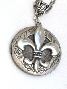 This stylish Steampunk locket is the perfect accessory for day or night.   The focal point of this locket is an brass Fleur De Lis stamping. The stamping has been mounted onto a floral antique silver