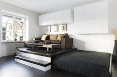 Practical storage solution in the living room of a small apartment - hidden bed in the platform