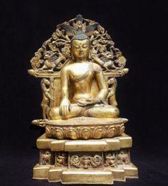 Beau Bouddha Sâkyamuni assis en Vajrasana sur un tertre à motifs, les mains en position de bhumisparsa mudra, position de prise de la terre à témoin, adossé à une importante mandorle à décor zoomorphe et symboles ésotériques. Bronze doré au mercure finement ciselé. Tibet XVIII-XIXeme. Ht: 37 cm.