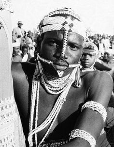 A young warrior wears a traditional headdress and cord armlets.