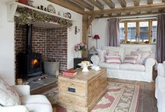 Cottage living room. Inglenook fireplace, log burner and dried hop garland. Rustic vintage trunk coffee table.