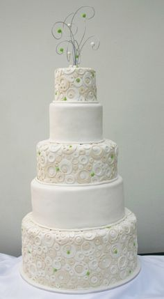 5 Tiered fondant wedding cake with contemporary circle design and wire scroll cake top