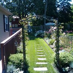 A clematis-covered arbor and grass-encircled stepping stones beckon visitors to this beautifully blooming side yard. | thisoldhouse.com/yourTOH