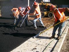 Workers raking asphalt in tight spaces for a Southern California development project.