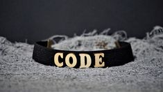 Finish off your look with this CODE super cute Letter Choker necklace.Take your outfit to the next level with this black wooden choker. * Length: 30 cm * Width: 2 cm * Chain link whit lobster clasp * Letters material: wood * Band material: elastic Available in black,red and white color