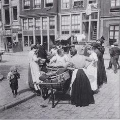 1915 Dames met baaien rokken en witte jakken met hun straathandel op de Lindengracht