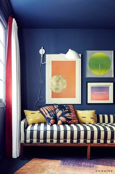 Cobalt walls with gallery wall and black and white striped sofa with tie dyed pillows.  Bench. Sofas. Stripes. Rug.