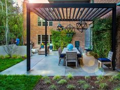 Contemporary Courtyard with Custom Pergola, Pendants and Dining Table