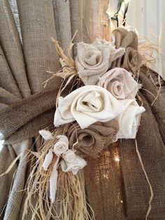 Fabric roses on tie backs for giant curtains on a barn — so perfect for a rustic chic wedding!