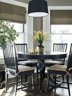 Finding Center        Subtle details can define a dining space as its own room even if it's not. A suspended drum shade anchors the dining area and a tall potted tree delineates the traffic path to it.