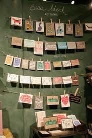 Using a simple line of string with pegs is an easy & cheap way to display cards
