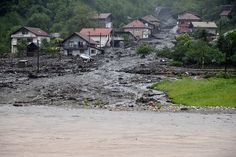 A view of a landslide and floodwaters around houses in the village of Topcic Polje, near the town of Zenica in Bosnia