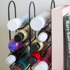 Un rangement à vin en fin de fer est utilisé pour ranger des produits de beauté et produits capillaires.