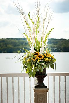 large urn filled with sunflowers and gladiolus and grass for the lakeside ceremony