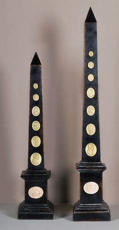 "2 Obelisks of different sizes but from the same family with Cameos ; Dim. of the Xlarge ; both in Black Chilean Pine 5""w x 5""d x 33""h"
