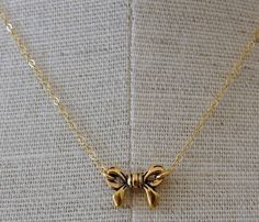 Tiny Gold Bow Necklace. Need this to wear with my side cross necklace :)