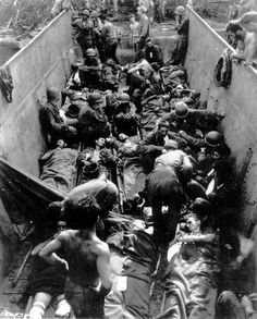 Description of  August 1943: Wounded American soldiers are seen as they lie aboard a lighter onshore at Munda Point, New Georgia island. (AP Photo)