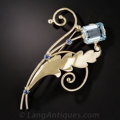 Tiffany & Co. Aquamarine and Sapphire brooch. Flowing, sapphire studded, golden leaves and stems culminate in a sky blue aquamarine, weighing 6.50 carats, in this wonderful work of wearable art by Tiffany and Co. - circa 1940s. This chic Retro brooch measures just shy of 3 inches high by 2 inches in width.