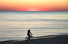 A biker takes a sunset ride along the coast at Mexico Beach.