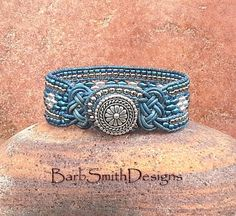 The Knotty One in Denim  This knotty girl features (2) double-strand Josephine Knots in Distressed Denim Leather cord. The center row is done in Petrol Blue and Silver Super Duo beads, and surrounded by (2) double rows of Nickel and Rainbow Petrol Blue seed beads. It closes with a beaded loop around a silver Bali button.  This bracelet fits up to a 6 3/4 - 7 wrist.  IMPORTANT NOTE ABOUT SIZING: Please measure your wrist with a tape measure. This is a custom made bracelet, so the sizing may…