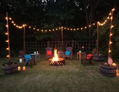 Outdoor living space with seating and fire pit. String lights on poles , whiskey barrels, fire ring, adirondack chairs, pillows, DIY fire pit backyard, simple patio, outdoor lighting, patio decor ideas, easy