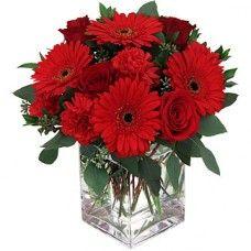 Cubo composto com um sortido de flores Vermelhas.
