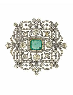 An early 20th century emerald and diamond brooch/pendant. The curved openwork cartouche shaped panel with central rectangular cut-cornered emerald within an old-cut diamond border, to the similarly-set scrolling foliate surround with four circular-cut diamond highlights and rose-cut diamond frame, 7.4cm long, with detachable pendant loop and brooch fitting, original fitted Garrard & Co. Ltd case with embossed R.L beneath a coronet to the lid.