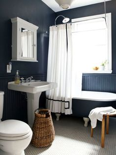 The sophisticated surprise of navy walls with a white floor and trim -- warmed by the wood and basket.