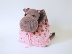 """Practice tapestry crochet to make the hippo print and form the bag. Then make the hippos head that will work as a lid and adds the fun touch to the design. The backpack straps can be crocheted for 3-6 year old kids (little girl in the picture is 3 years old). Backpack is one size only.  SKILL LEVEL Intermediate: This design includes crochet basic stitches, a mid-level tapestry crochet pattern, easy shaping and finishing techniques.  FINISHED SIZE 10.2"""" x 9.3""""/ 26 cm x 23.5 cm  STITCHES A..."""