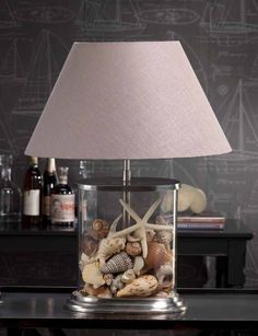 A lamp that changes with the seasons. Fill the clear glass lamp base with seashells for the Summer or to accent your beach style. The unique oval shape takes up less space on an end table or night stand. Ocean Home Decor, Beach House Decor, Coastal Decor, Clear Glass Table Lamp, Glass Lamp Base, Fillable Lamp, Shell Lamp, Chandelier Art, Jar Lamp