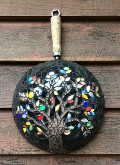 Mosaic frypan hanging near the barbecue. The tree and leaves are China with a few glass gems and ceramic tile background.