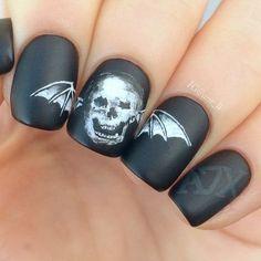 Matte black Halloween nail design with skull.