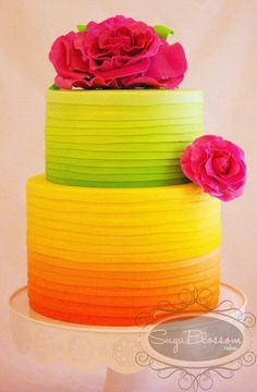 Citrus colored ombre wedding cake with bright fuchsia flowers,