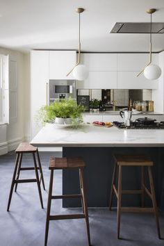 This kitchen-diner has a more urban feel, with concrete flooring flowing through to a chic, city-dwellers' version of a garden room. Classic, enduring surfaces including brass, marble and timber make this hard-working space functional and contemporary. #kitchenideas #kitchenisland #kitchendesign
