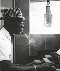 Nat King Cole enjoys a smoke while he plays his tunes on a piano.