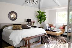 """""""The master bedroom is our latest addition to the house,"""" says Bhargava. """"We wanted a sanctuary."""" She chose the Robertson bed by Williams-Sonoma Home for its clean lines and the low headboard, which makes the ceiling feel higher. Rustic Luxe bedding and antique mercury glass lamp by Pottery Barn. A vintage leather ottoman is paired with a Wilshire sofa, slipcovered in white Classic Linen, by Williams-Sonoma Home."""