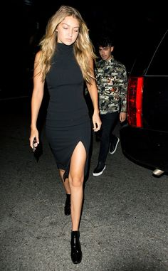 Gigi Hadid wears a black high-neck slit dress with black patent leather ankle boots