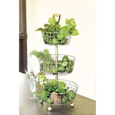 """Tiered Wire Basket, $89 Dimensions: Overall: 29 3/4""""H X 13 3/4"""" Diameter Top Basket: 4""""H X 9 1/2"""" Diameter Middle Basket: 4""""H X 11 1/2"""" Diameter Bottom Basket: 4""""H X 13 3/4"""" Diameter Construction: Made of iron with wooden handle. Country of Origin: China"""
