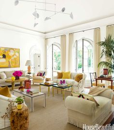 """Bursts of sunny yellow and fuchsia refresh traditional architecture in the living room of this Naples, Florida, home designed by Jesse Carrier and Mara Miller of Carrier and Company. A hanging mobile light fixture by David Weeks """"artfully fills"""" the soaring ceiling. Love seats in Larsen's Bouquet Garni II bring texture and pattern to glossy Venetian plaster walls."""