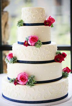 Tort weselny z granatowymi wstążkami i różowymi kwiatami
