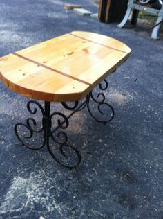Antique wrought iron bench with pine top and walnut inlay.