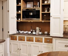 Great storage for microwaves and draws underneath for organising. Classic painted kitchen by Tom Howley