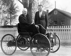 Henry Ford seated on his Quadricycle in 1946, while his grandson, Henry Ford II stands beside him. The Quadricycle, which was assembled in 1896, was the first vehicle Henry Ford produced.