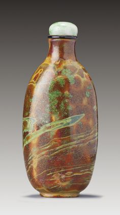A 'REALGAR' GLASS SNUFF BOTTLE QING DYNASTY, LATE 17TH / MID-18TH CENTURY the opaque, variegated scarlet, yellow, and green glass with extensive surface crizzling, with a flat lip and a recessed, slightly convex foot surrounded by a protruding flat footrim; the jadeite stopper with a glass stopper