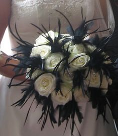 A classic hand-tied wedding bouquet with a bold contemporary twist. Black feathers are combined with white roses to dramatic effect in this monochromatic bouquet.