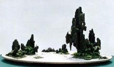 "This large landscape on a 59"" white marble slab created by Qingquan 'Brook' Zhao showcases one of three forms of penjing found in China today. The main artistic medium used here is rock; plants are used for accent only. This is a unique Chinese creation – it would and should never be called bonsai."