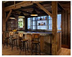 This rustic bar area combines exposed beams with other industrial elements, like unfinished wood, for an upscaled country vibe