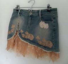 Super cute upcycled denim mini skirt. Lace up details on front and back and embellished with blush and cream lace on the lower hem edges and