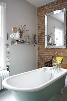 Une vue de baignoire en blanc et un mur avec des briques